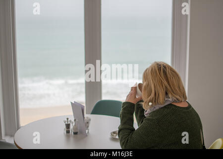 Woman drinking tea in front of a window looking out to the beach and sea at St Ives Cornwall. - Stock Photo