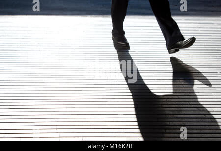 Blurry one  man's  legs silhouette and shadow on city street patterned passage walkway in black and white - Stock Photo