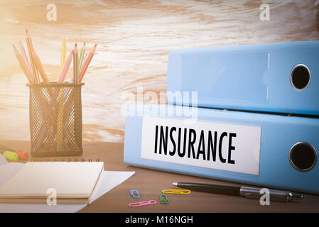insurance, Office Binder on Wooden Desk. On the table colored pencils, pen, notebook paper - Stock Photo