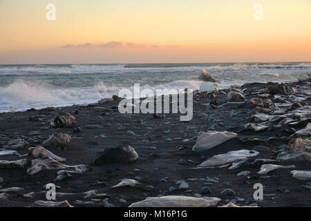 Ice washing up on the volcanic black sand beach near the Jökulsárlón glacier - Stock Photo