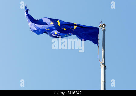 Flag of the European Union on the flagpole against the blue sky. - Stock Photo