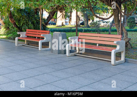City park or street with green trees and tile - two neat benches made of concrete and wood, between the rubbish - Stock Photo