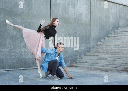 Slender ballerina dances with a modern dancer. Dating lovers. Performance in the streets of the city. - Stock Photo