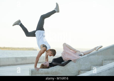Slender ballerina dances with a modern dancer. Dating lovers. Passion and romance of dance. He stands on his hands. - Stock Photo