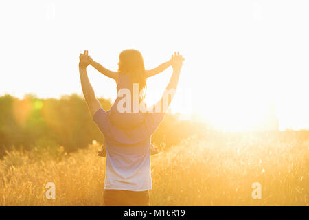 Family values. Father and daughter meet the sunset. He will put the girl on his shoulders and hold her hands. Piggyback Stock Photo