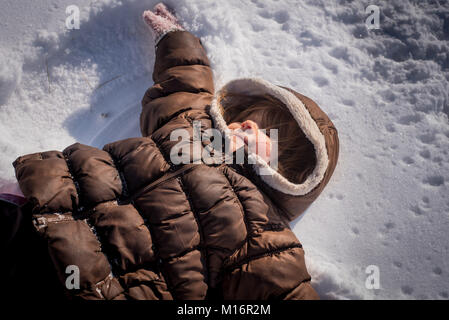 A three-year old girl makes a snow angel in the snow in northeast United States. - Stock Photo