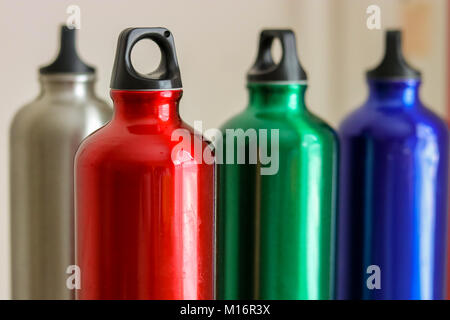four Metal water bottles silver red green blue - Stock Photo