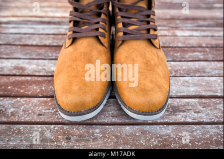 pair of mens tan suede boots on a wooden floor. - Stock Photo