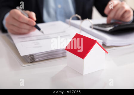Close-up Of A House Model In Front Of Businessperson Calculating Bill On Desk - Stock Photo