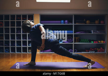 Portrait of beautiful young woman wearing sportswear working out in studio. Fit sporty girl stretching. Side view - Stock Photo