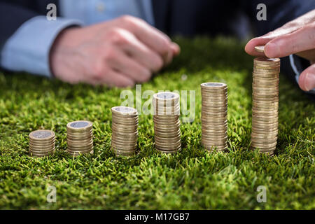 Close-up Of A Businessperson's Hand Stacking Coins On Green Grass - Stock Photo