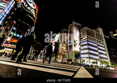 Tokyo, Japan. Pedestrians cross the street at the heart of Ginza District in Tokyo. Ginza crossing at night. Blurred - Stock Photo