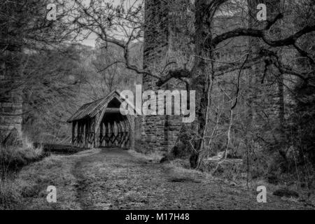 This rustic little shelter sits immediately below one of the arches of the Camps Viaduct in Almondell Country Park, - Stock Photo