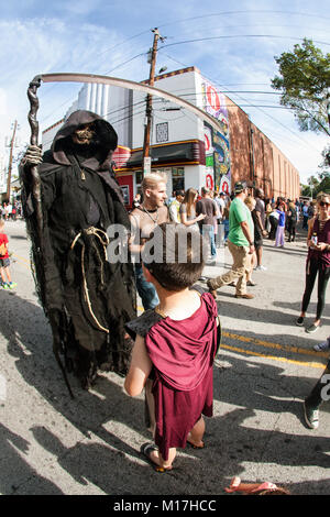Atlanta, GA, USA - October 21, 2017:  A boy interacts with person wearing menacing grim reaper costume and holding - Stock Photo