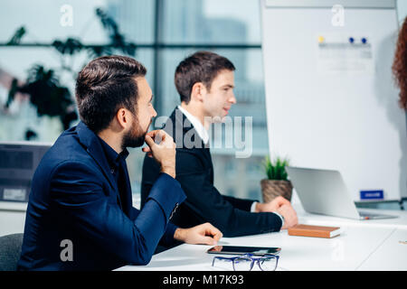 Business woman giving presentation to colleagues in office - Stock Photo