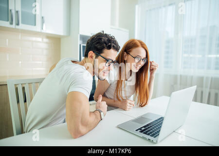 Shocked couple watching something on laptop at home - Stock Photo