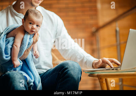 man working at desk at home with laptop, holding cute babys, looking at screen