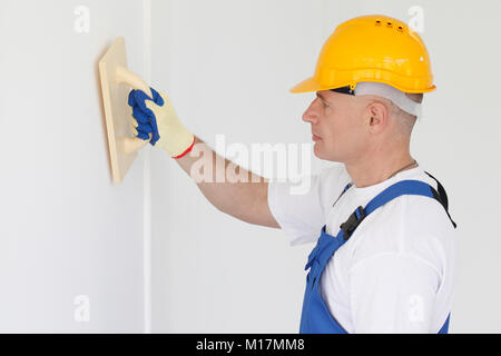 Builder working with grinding tool aligning wall indoors - Stock Photo