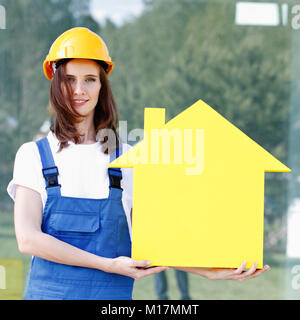 Forewoman presenting house symbol, construction concept - Stock Photo