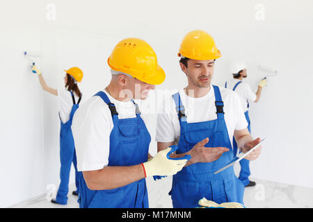 Workers discuss renovation project using digital tablet - Stock Photo