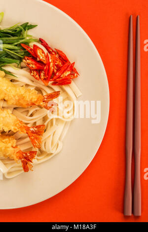 Japanese Style Tempura Prawns With Udon Noodles Chilli and Spring Onions Against A Red Background - Stock Photo