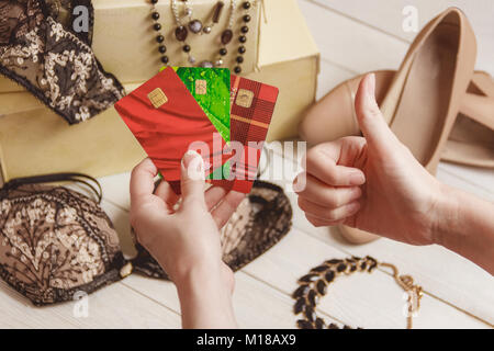 consumerism, finances and sale concept - close up of female hand with credit card over women clothing and accessories - Stock Photo