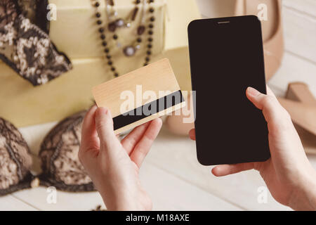 consumerism and sale concept - close up of female hand with credit card and smartphone over women clothing, accessories - Stock Photo