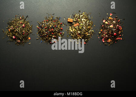 Dry tea collection of different types on black background - Stock Photo