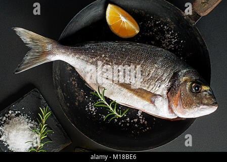 Delicious fresh fish on dark vintage background. Healthy food diet or cooking concept - Stock Photo