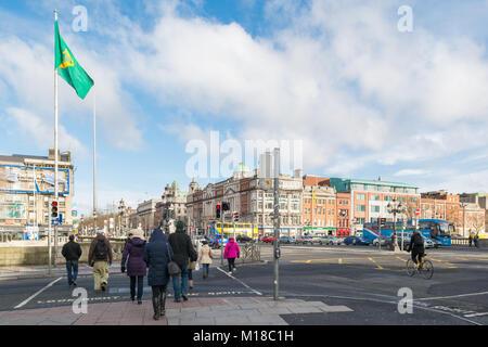 pedestrians crossing the road at O'Connell Bridge, Dublin facing towards O'Connell Street, Dublin, Ireland, Europe - Stock Photo