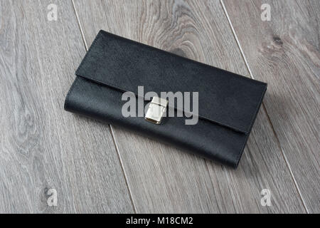 Black leather wallet on a brown wooden surface - Stock Photo