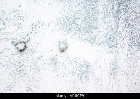 Two bolts in old metal sheet painted in white with brush spots, industrial background texture - Stock Photo