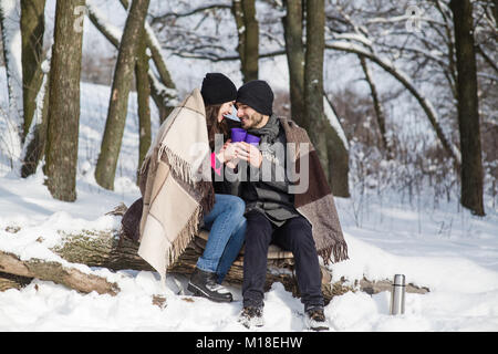 Lovely couple sitting on log under plaid in the winter park - Stock Photo