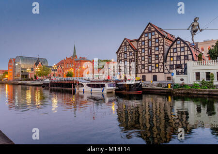 Brda river in Bydgoszcz (ger. Bromberg), 'Man crossing a river' sculpture of man balancing on a wire, old granary, - Stock Photo