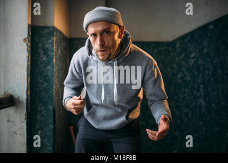 Aggressive male robber with knife strikes fear. Street bandit waiting for victim. Crime concept, robbery attack - Stock Photo