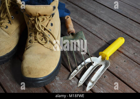 Pair of work boots with garden tools on a wooden deck - Stock Photo