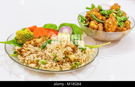 Indian meal of veg fried rice and spicy chicken kosha isolated on white background. A popular Bengali food. - Stock Photo