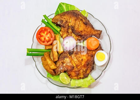 Crispy spicy fried pomfret fish with french fries and garnished with vegetables and sliced egg. A popular Bengali - Stock Photo