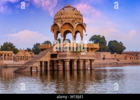 Gadi Sagar lake (Gadisar) Jaisalmer Rajasthan with ancient temple and archaeological ruins at sunrise. - Stock Photo