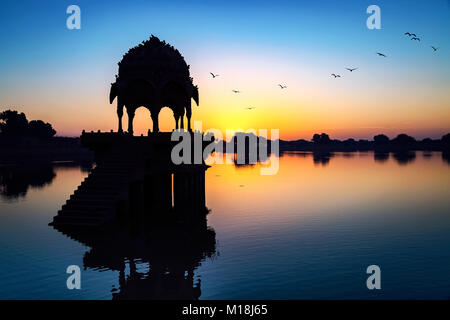 Gadi Sagar lake (Gadisar) at Jaisalmer, Rajasthan with ancient temple at dawn. - Stock Photo
