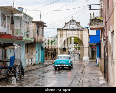 Holguin, Cuba - August 31, 2017: View of an American classic car driving towards the entrance to a cemetery - Stock Photo