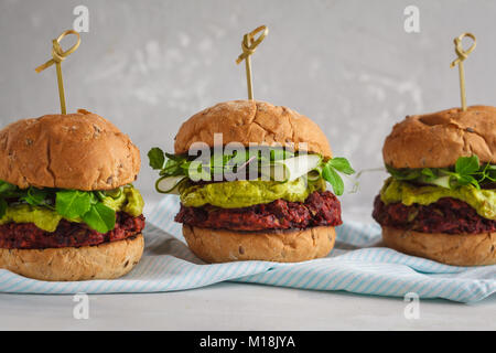 Vegan beet burgers with vegetables, guacamole and rye bun with green juice. Healthy vegan food concept. - Stock Photo