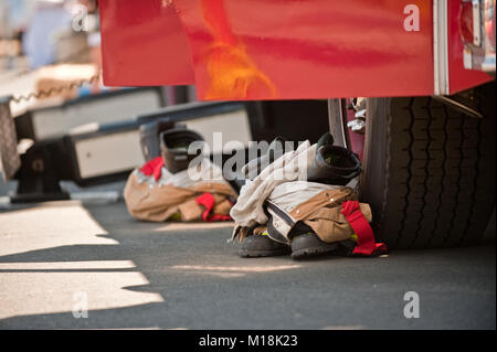 Close up view of pairs of fire boots and fire pants outside a fire truck at a public event - Stock Photo