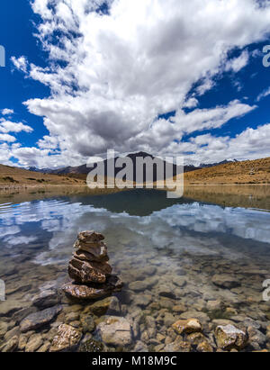 Reflections in the Dhankar lake with clouds floating across the Spiti valley - Stock Photo