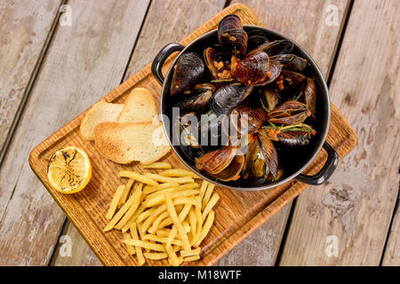 Many mussels in saucepan and side dish. - Stock Photo