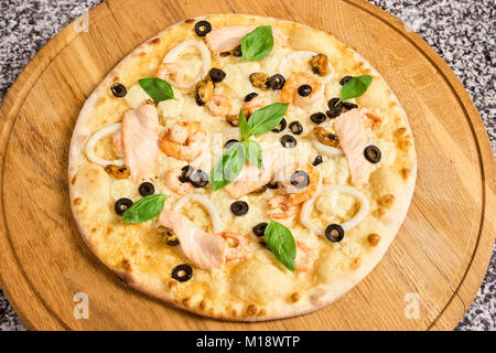Pizza with seafood, olives and basil leaves. - Stock Photo