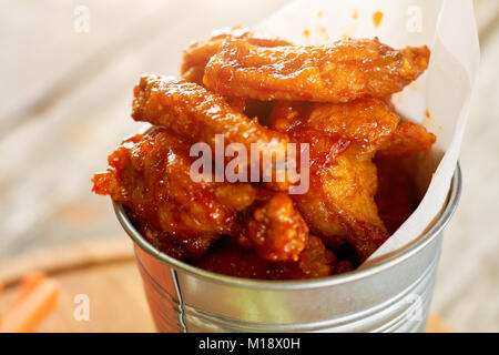 Juicy fried chicken meat pieces in sause, close up. - Stock Photo