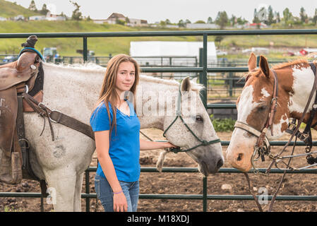 Girl and two horses enjoy a quiet moment behind the scenes during the 90th Williams Lake Stampede, one of the largest - Stock Photo