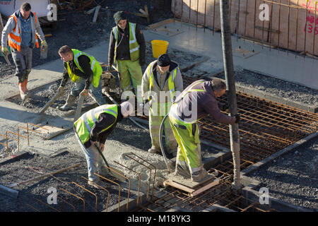 Workmen  in high visibility flourescent jackets on building, pouring concrete into foundations - Stock Photo