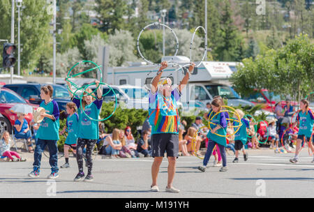 First Nations elder leads children in the performance of a traditional hoop dance at the annual Stampede Parade - Stock Photo